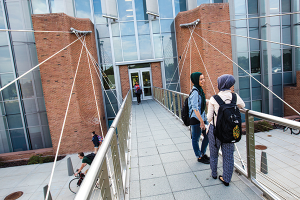 Students wearing hijabs on Science complex bridge