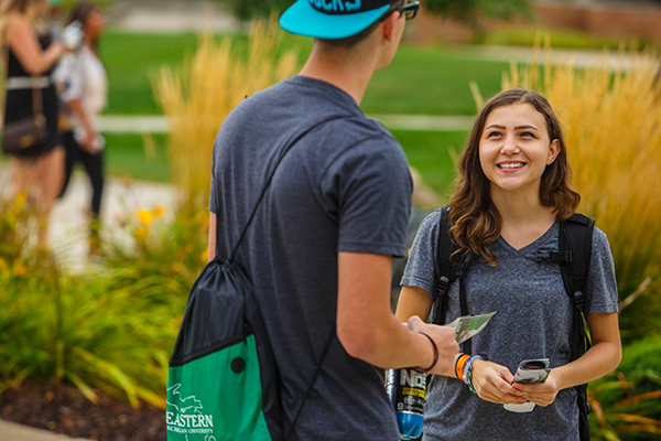 Students having a conversation outside on campus.