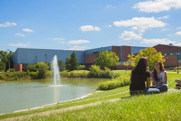 Two females students sitting on the lawn outside the student center in Spring near a flowing fountain.