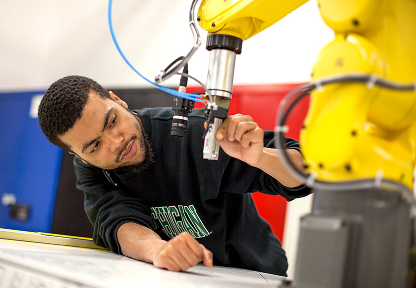 A student works on robotic machine in lab.