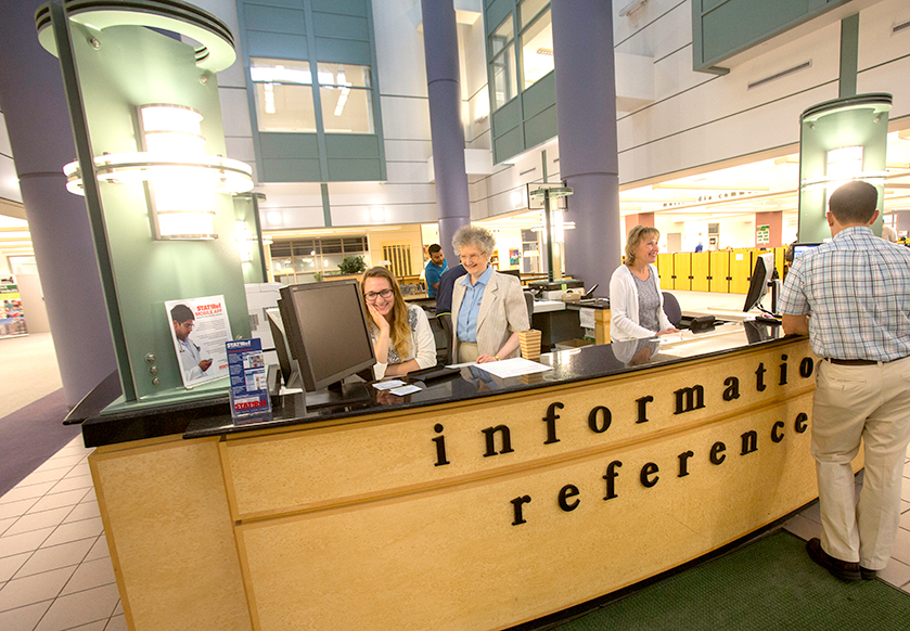 Student and staff working at Halle Library information desk.