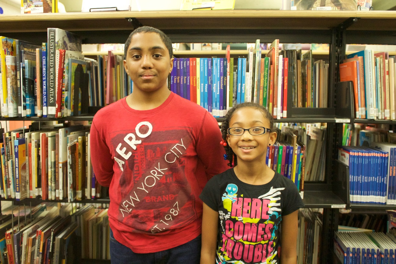 Aaron and Tia smile at the camera and stand in front of a bookshelf full of books.