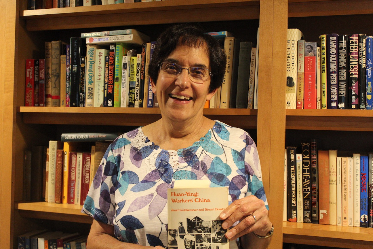 Janet smiles at the camera in front of a bookshelf full of books and she holds up a book.