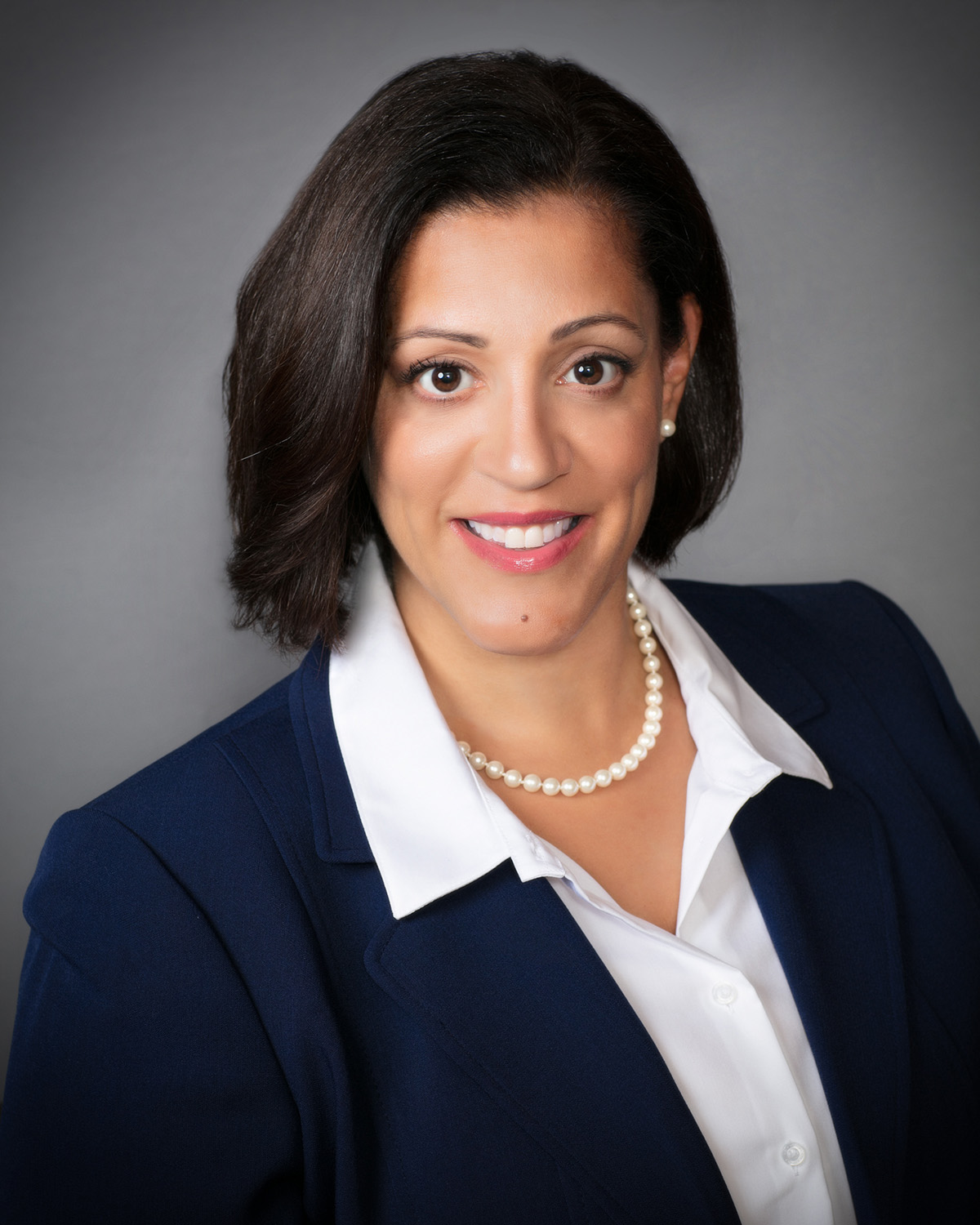 Anita I. Martinez is wearing a dark blue suit with a white collar shirt and a white necklace.