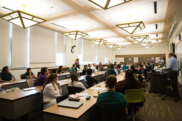 A photo shows a classroom of students listening to a lecture.