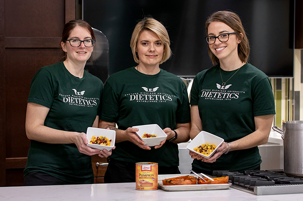Three female dietetics students holding up food.
