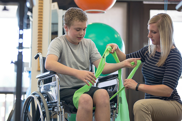 A student helps a patient in a wheelchair.
