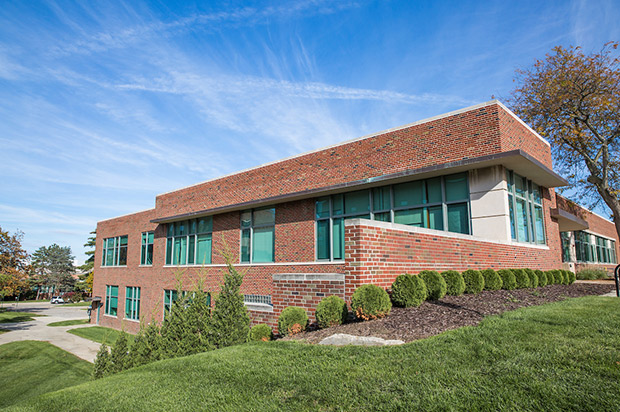 An image of the outside of Rackham - a brick building with green tinted windows.