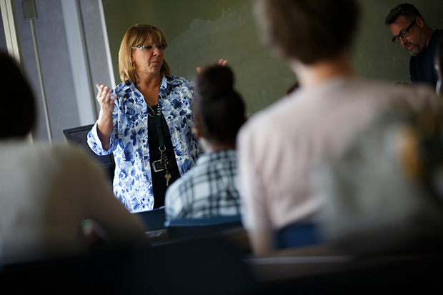 A female professor teaches a class of students.