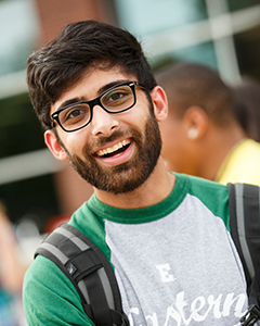 A male student with a beard and glasses smiles at the camera.