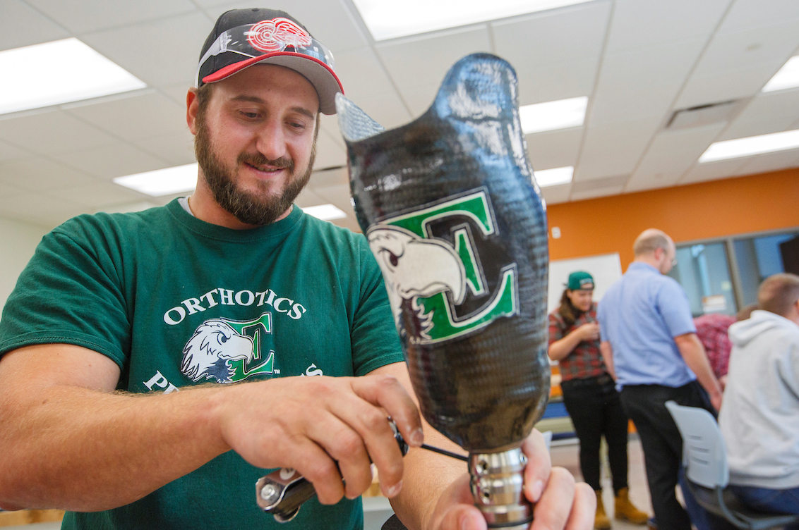 A student in EMU green works on a prosthetic leg with the EMU eagle logo on it.