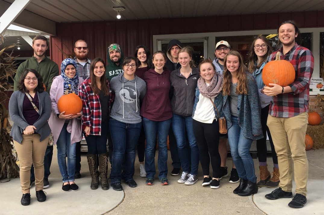 A group of students stand outside holding pumpkins.