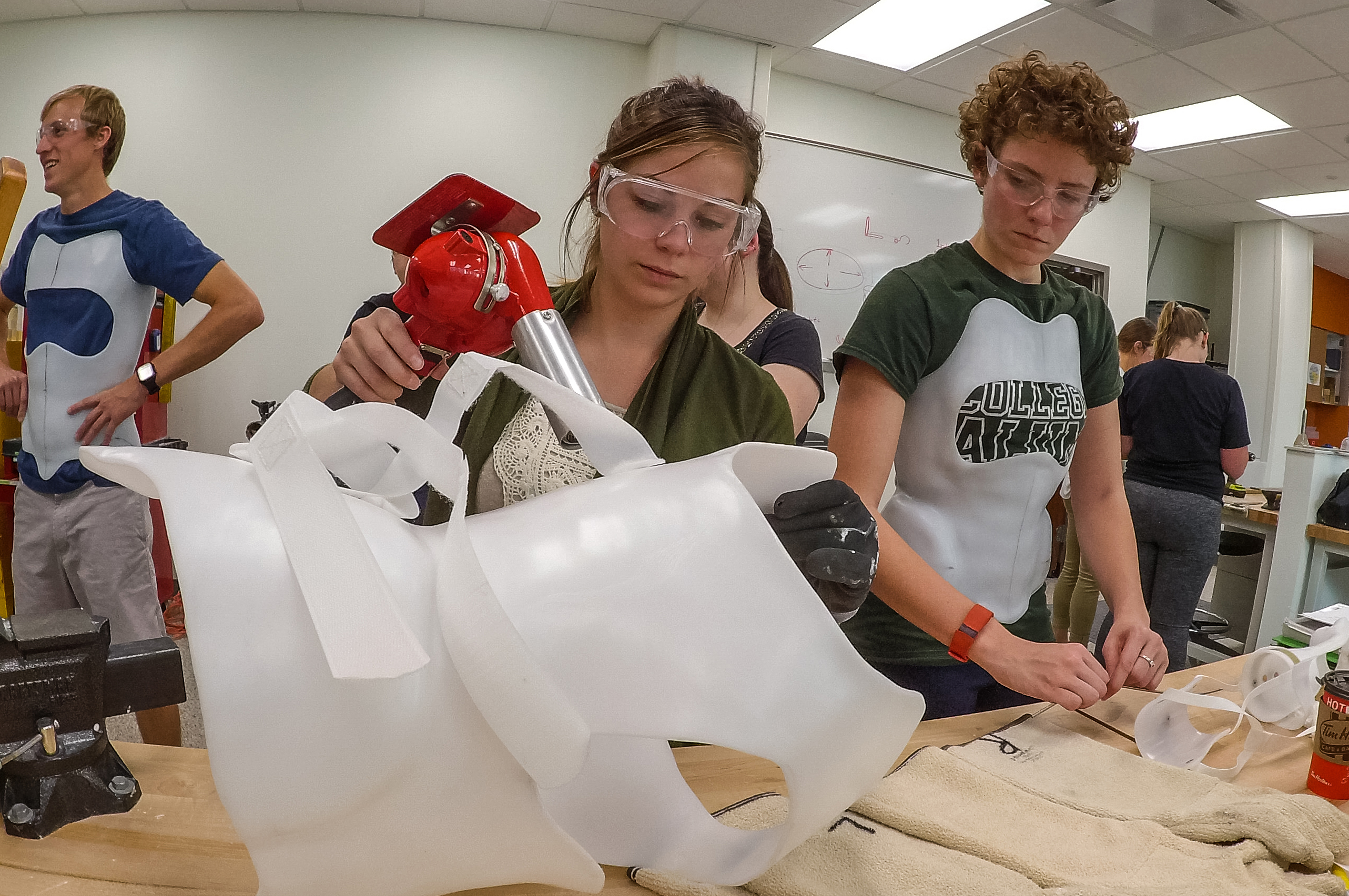 Two female students work on a prosthetic.