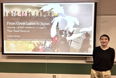 A photo of Junko Kondo standing next to her presentation.