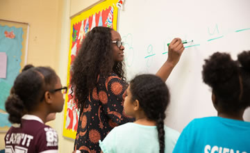 a photo of a student teacher writing on a white board with young students gathered around her