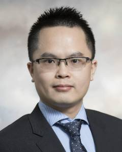 This is a photo of Weitian Tong wearing a black suit with glasses, a blue collar shirt and a navy blue tie.