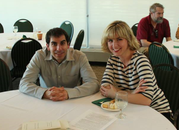 A man and a woman sit at a table eating and smiling.