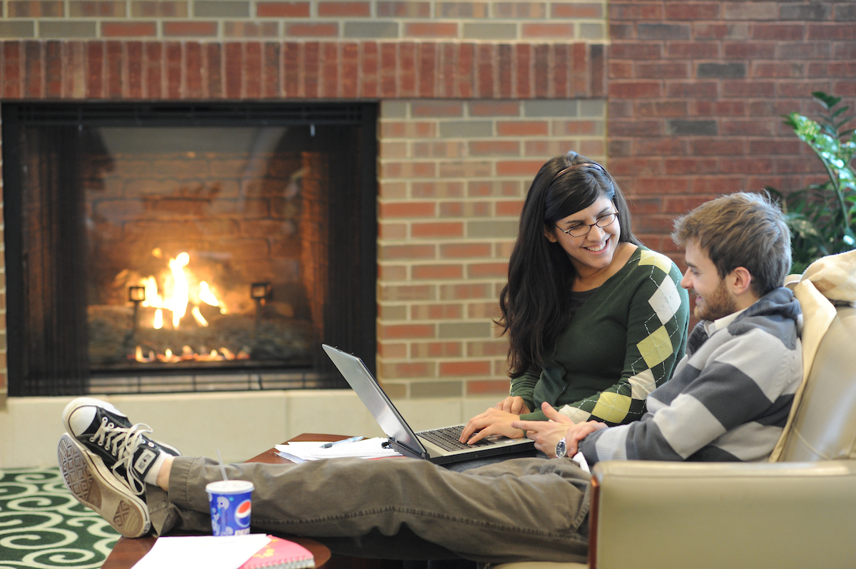 Two students reading by a fireplace