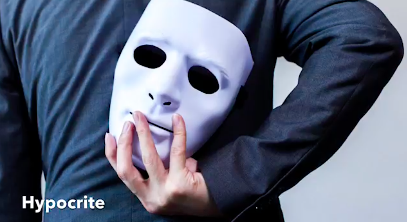 A white person whose face is hidden is wearing a long-sleeved black Tshirt holds a white mask behind their back.