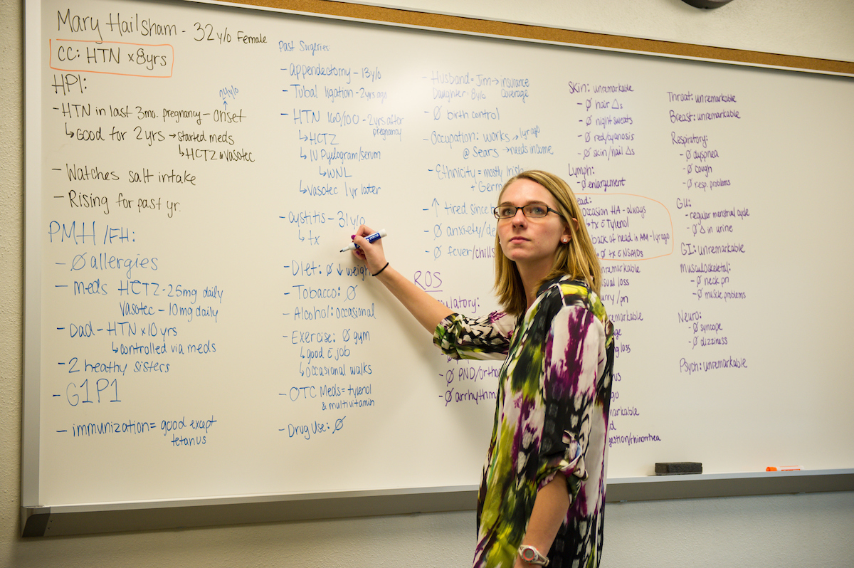 An instructor writing on a white board