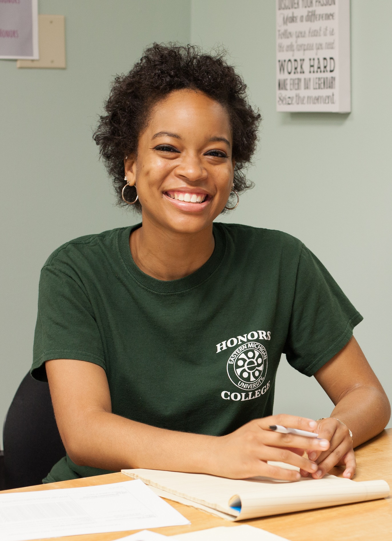 Brianna Moore is wearing a green t-shirt with the Honors College logo.