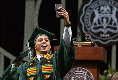 male graduate in green regalia taking selfie on stage at commencement
