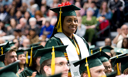 female mcnair scholar wearing cap and gown stands at commencement
