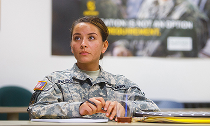 woman in military dress, sitting in a classroom
