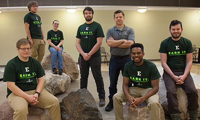six students and professor posing by indoor rocks at Science Complex