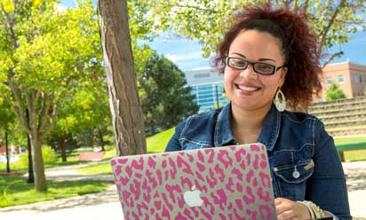female student outside, with pink leopard print laptop