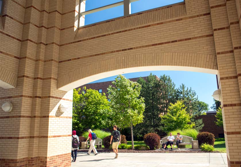 Student walk under the brick arch of Halle Library at one of the best universities in Michigan.