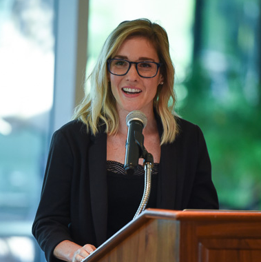 A headshot photo of Holly Huffnagle speaking at a podium.