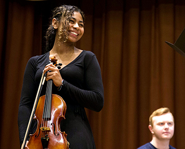 A female student with violin smiles during rehearsal.