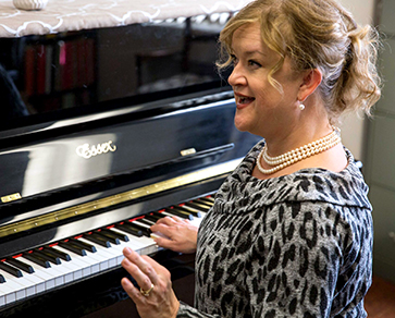 An instructor teaches while seated at the piano.