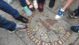 Students point to a distance marker with their shoes in Spain.
