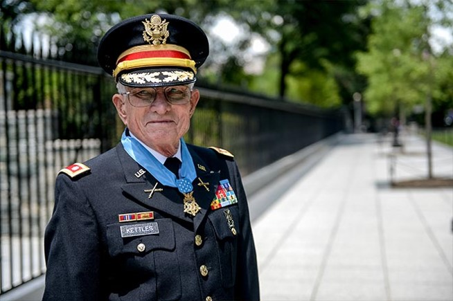 A photo of Lt. Col. Charles Kettles standing by a black fence outdoors.